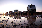 Truck tractors and Army PLS vehicles with containerized cargo are staged and ready in a muddy lot, waiting to begin a morning combat convoy run from Balad Air Base to forward operating base Caldwell, Iraq, 15 Jan 2006. (U.S. Air Force photo by Master Sgt. Lance Cheung)<br />