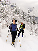 Two women snowshoe through a snowy forest in early December at Snoqualmie Pass, Washington, USA