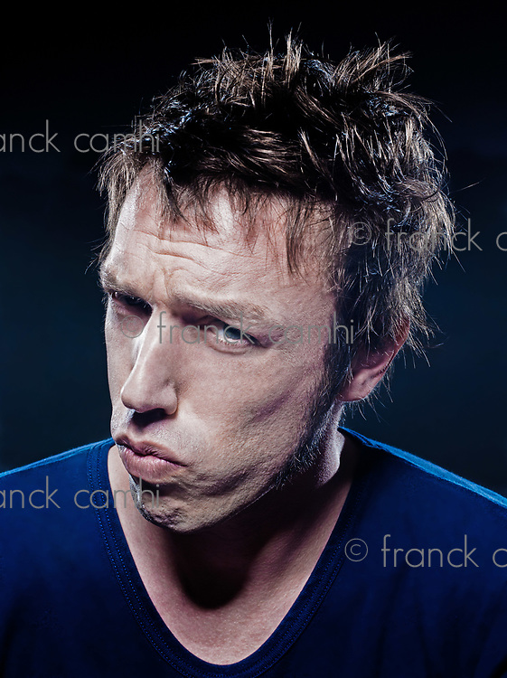 studio portrait on black background of a funny expressive caucasian man frowning upset