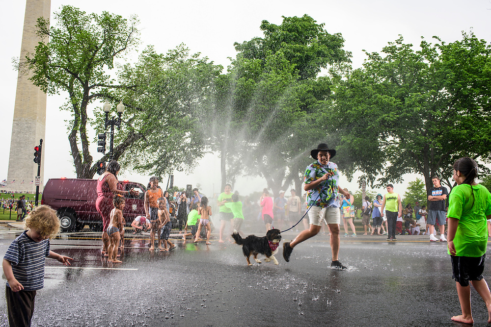 Washington, D.C. - April 29, 2017: People play in sprinklers set up by the D.C. fire department on Constitution Ave. after the People's Climate Movement in Washington D.C. Saturday April 29, 2017. <br /> <br /> <br /> CREDIT: Matt Roth for The League of Conservation Voters