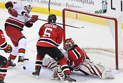 Feb 16; Newark, NJ, USA; New Jersey Devils goalie Johan Hedberg (1) makes a save on Carolina Hurricanes left wing Sergei Samsonov (14) while New Jersey Devils defenseman Andy Greene (6) defends during the third period at the Prudential Center. The Devils defeated the Hurricanes 3-2.