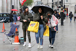 © Licensed to London News Pictures. 04/05/2019. London, UK. Tourists shelter under an umbrella in Trafalgar Square as it starts rain. Photo credit: Dinendra Haria/LNP