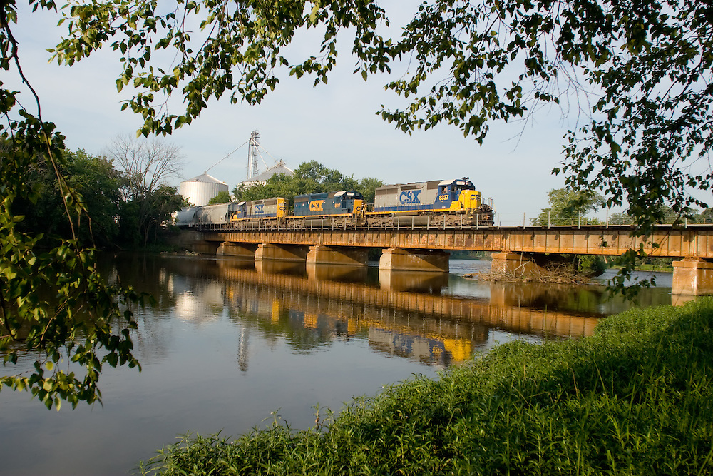 Crossing the Kankakee River, a northbound CSX freight train is reflected in the calm waters below on this warm summer morning in the small eastern Illinois town of Momence.