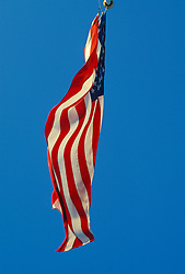 American flag blowing in the wind against a clear blue sky