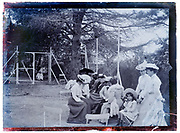 women and child at a a fenced off children playground 1900s France Paris