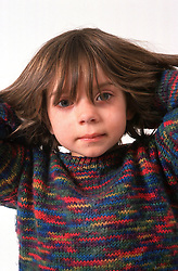 Portrait of young girl playing with hair,
