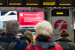 © Licensed to London News Pictures. 24/12/2013. London, UK. People waiting for their trains at Paddington Rail station as they journey out of London for the Christmas break view warning signs explaining that services are experiencing disruption as a result of adverse weather conditions. Photo credit : Richard Isaac/LNP