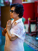"22 AUGUST 2017 - BANGKOK, THAILAND: A woman prays during a ceremony on the first day of Hungry Ghost Month at the Poh Teck Tung Shrine in Bangkok's Chinatown. The seventh lunar month (August - September) is when many Chinese believe Hell's gate will open to allow spirits to roam freely in the human world. Many households and temples hold prayer ceremonies throughout the month-long Hungry Ghost Festival (Phor Thor) to appease the spirits. During the festival, believers will also worship the Tai Su Yeah (King of Hades) in the form of paper effigies which will be ""sent back"" to hell after the effigies are burnt.      PHOTO BY JACK KURTZ"