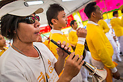 14 OCTOBER 2012 - BANGKOK, THAILAND:   A musician performs in the merit making area on the first day of the Vegetarian Festival in Bangkok's Chinatown. The Vegetarian Festival is celebrated throughout Thailand. It is the Thai version of the The Nine Emperor Gods Festival, a nine-day Taoist celebration beginning on the eve of 9th lunar month of the Chinese calendar. During a period of nine days, those who are participating in the festival dress all in white and abstain from eating meat, poultry, seafood, and dairy products. Vendors and proprietors of restaurants indicate that vegetarian food is for sale at their establishments by putting a yellow flag out with Thai characters for meatless written on it in red.     PHOTO BY JACK KURTZ