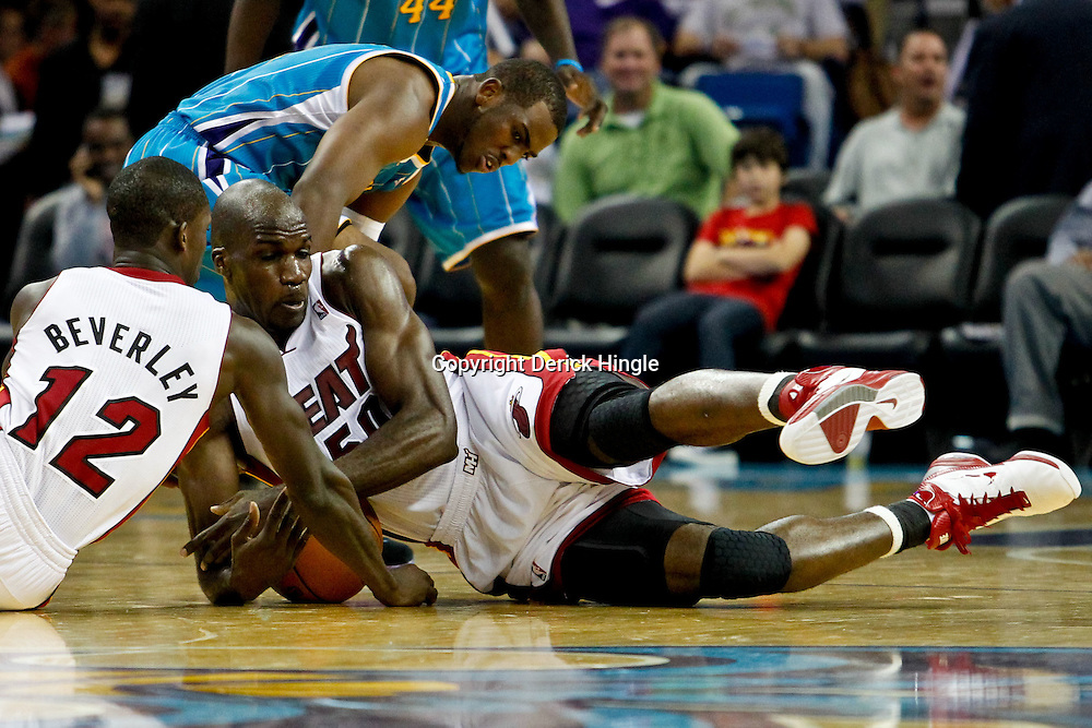 October 13, 2010; New Orleans, LA, USA; Miami Heat center Joel Anthony (50) and point guard Patrick Beverley (12) scramble for a loose ball with New Orleans Hornets point guard Chris Paul (3) during the second half of a preseason game at the New Orleans Arena. The Hornets defeated the Heat 90-76. Mandatory Credit: Derick E. Hingle