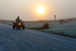 © Licensed to London News Pictures. 20/01/2020. Howey, Powys, Wales, UK. A quad bike negotiates the treacherous icy conditions at dawn on a mountain road near Howey in Powys, Wales, UK. Photo credit: Graham M. Lawrence/LNP