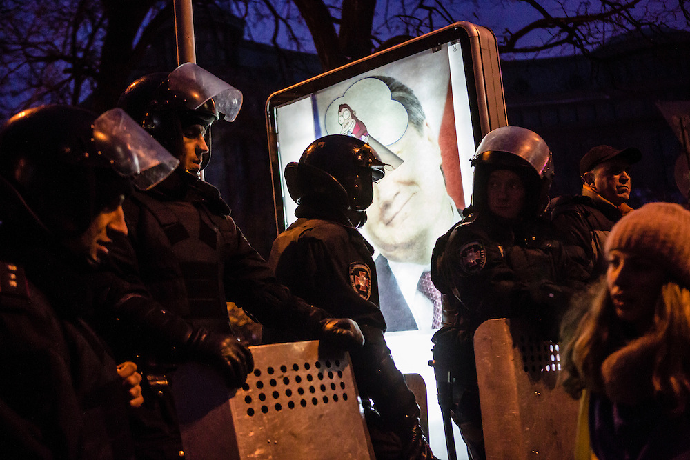 KIEV, UKRAINE - DECEMBER 15: Police form a blockade near Independence Square, the site of a large anti-government rally, in front of a defaced poster of Ukrainian President Viktor Yaunkovych on December 15, 2013 in Kiev, Ukraine. Thousands of people have been protesting against the government since a decision by President Yanukovych to suspend a trade and partnership agreement with the European Union in favor of incentives from Russia. (Photo by Brendan Hoffman/Getty Images) *** Local Caption ***