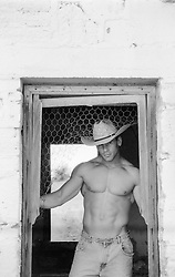 shirtless muscular cowboy in a barn