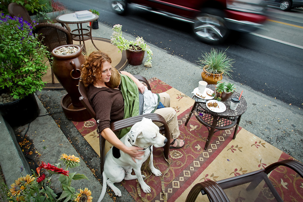 Anissa Duwaik relaxes in a parking space Friday along Sherman Avenue with her son Jaddin, 3, and her dog Rosko. The display locally was part of a nationwide event called PARK(ing), that saw artists, activists and citizens temporarily transform parking spaces into public parks and other social spaces.