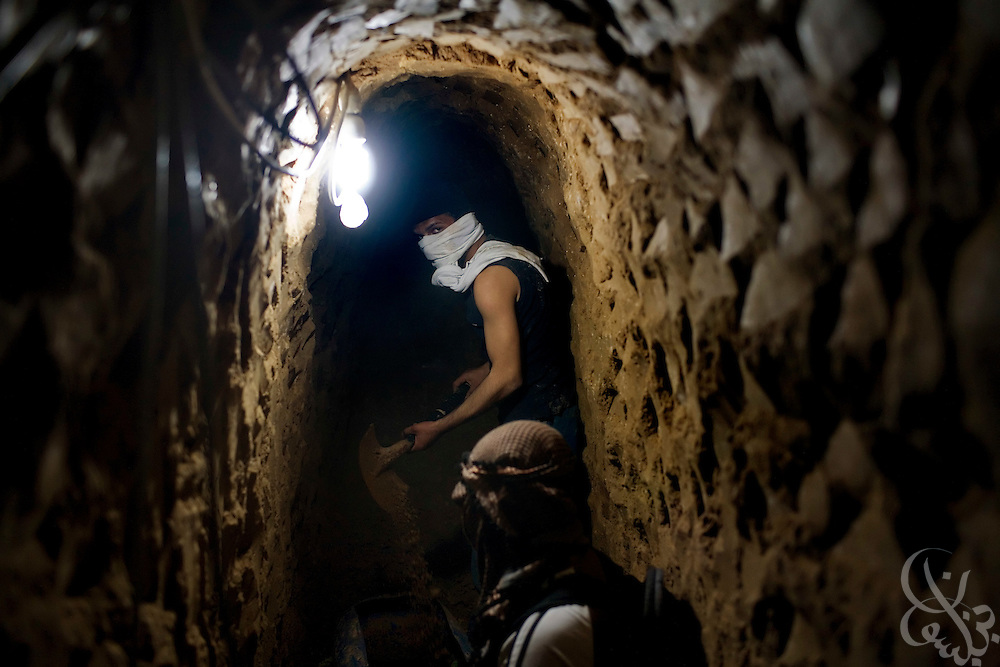 Palestinian workers dig out a bombed section of a smuggling tunnel on the Gaza-Egypt border in Rafah, Gaza January 22, 2009. Since the end of the 22 day Israeli military operation that included heavy airstrikes on the tunnel area, Palestinians have been busy reopening the undamaged tunnels, and rebuilding more heavily damaged or destroyed ones.  ..
