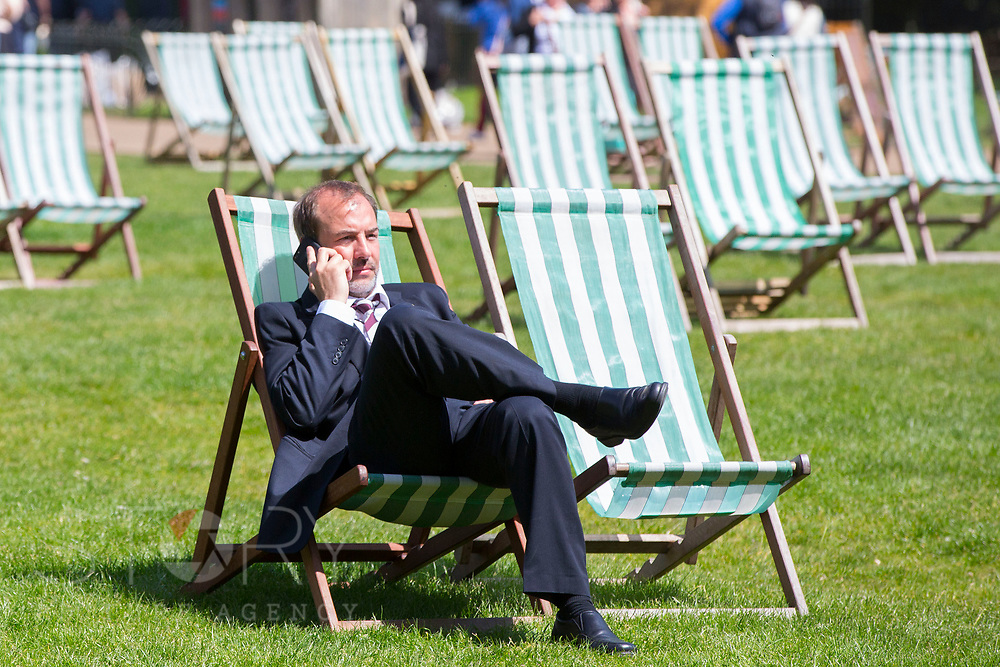 UNITED KINGDOM, London: 14 May 2019 <br /> A businessman talks on the phone as he relaxes in the sunshine in Green Park on another fine day of weather across The UK. Temperatures are set to reach 19C in the capital and potentially higher in the Midlands.