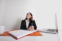 Businesswoman using cell phone at office desk