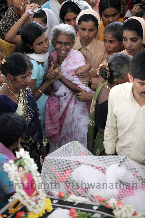 The grand mother of an Air India Express crash victim mourns over the coffins of her daughter and grand daughters  during their funeral service  at the St. Alphonsa Catholic Church, on May 23, 2010 in Mangalore. H.Rosaline and her two daughters H.Goldine and H.Gloria were passengers of the Air India Express Boeing 737-800 series aircraft arriving from Dubai, with 166 people onboard. Th flight overshot the runway on landing in Mangalore and crashed into a forest. Airline officials say 8 survivors have been rescued with 158 others feared dead. (Photo by Prashanth Vishwanathan/Getty Images)