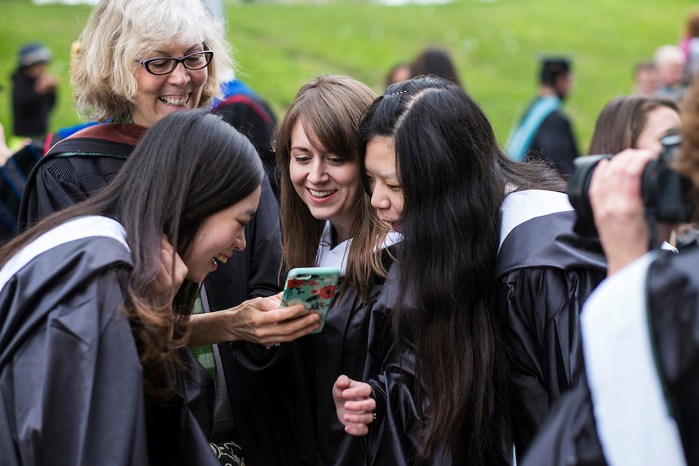 VisCom graduate students gather around to look at a photo on Professor Julie Elman's iPhone before the start of Ohio University's Graduate Commencement ceremony on Friday, May 1, 2015.  Photo by Ohio University  /  Rob Hardin
