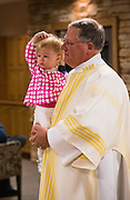 A deacon holds his granddaughter in the welcoming area of St. Thomas More Church in Appleton. (Sam Lucero photo)