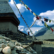 A monk walks under prayer flags and past a chorten at Rongbuk Monastery, Tibet [China], with the North Face of Everest rising behind.