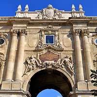 Lions' Gate at Buda Castle in Budapest, Hungary<br /> Lions' Gate is the transition from the Western Forecourt to the Lion's Courtyard. Between the four columns with Corinthian capitals are two sculptures representing Nike, the Greek goddess of victory. Anchoring the sides are two statues in niches crowned with Turuls from Hungarian mythology. On top of the arch is the small coat of arms of Hungary as it appeared in the mid-19th century until 1918.