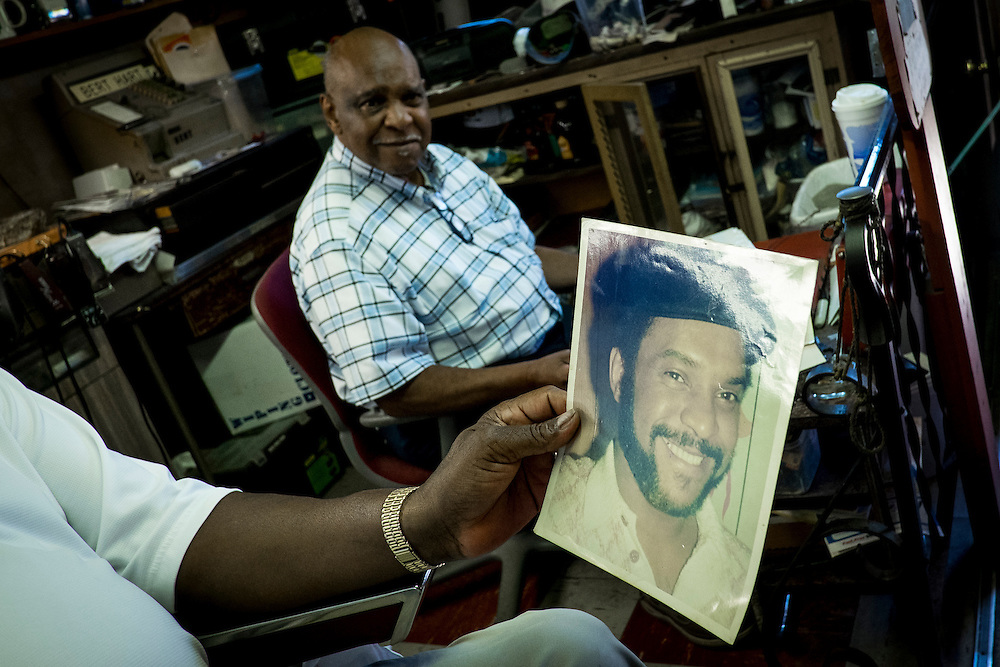 A customer looks at an old photograph of Bert Hart from the 1960's.<br /> <br /> 80-year-old Hart has been cutting hair in his Aliquippa barber shop for the past 60 years. Hart moved to Aliquippa in the boom times of the 1960&rsquo;s and opened Bert&rsquo;s Barber Shop in 1966.<br /> <br /> At that time the town was home to over 26,000 people but most of the homes and businesses along his street are gone as well as most of the people.<br /> <br /> At one time Hart owned three adjacent buildings, housing a bar, apartment building and the barber shop, in the Plan 11 neighborhood.<br /> <br /> The three-chair shop is a place where people hang out here and talk about everything from politics to religion and sports as well as the good old days when Aliquippa was thriving.