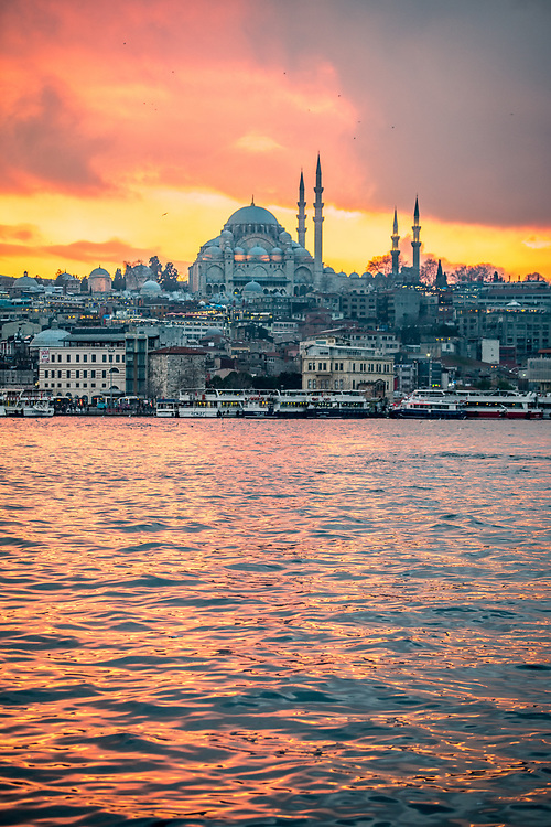 The sun sets over Suleymaniye Mosque and the city of Istanbul, Turkey creating a warm glow on the waters of the Golden Horn.
