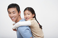 Young Girl Getting Piggyback Ride with Father side view