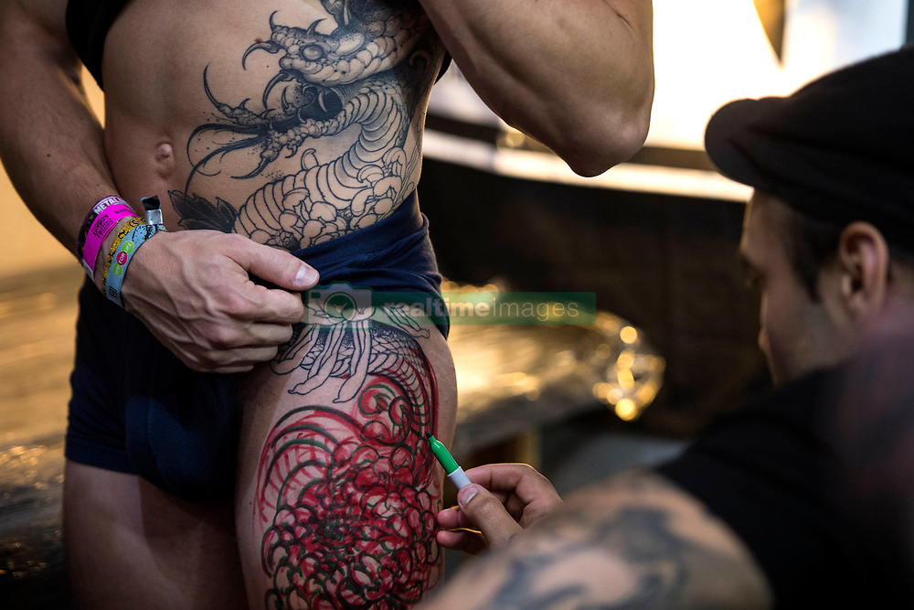 A man is given a tattoo during the International tattoo convention at Tobacco Dock in east London.