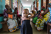 14th month old Jennifer has just been discharged, she waits with her mother in the corridor to receive a prescription for medication before returning home to her village. St Walburg's Hospital, Nyangao. Lindi Region, Tanzania.