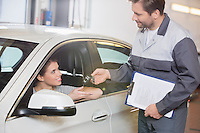 Automobile mechanic giving car key to female customer in workshop