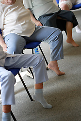 Group of older people doing leg exercises at a keep fit class,