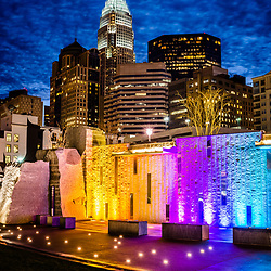Charlotte cityscape at night photo with Romare Bearden Park colorful waterfall wall and downtown Charlotte buildings against a deep blue sky and clouds. Charlotte, North Carolina is a major city in the Eastern United States of America.