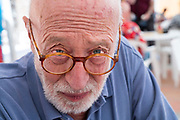 70+ man looking over his glasses direct into the camera