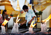 Buddhist and Nat worship devotional candles. The Shwedagon Pagoda complex, Yangon, Myanmar.