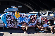 Argentina fans sit in the shade at the site set up for football fans who had nowhere to stay but the tents, campervans, cars and caravans that they had bought with them. The site, at the Terreirao Do Samba, Rio de Janeiro, Brazil, was arranged by the city government once they realised the number of fans in this situation was significant and rather than having them scattered about the sity they offered secure, enclosed accommodation with sanitation and water. The majority of fans at the site were Argentinian but there were also people from Chile, USA, Uruguay and Colombia. Photo by Andrew Tobin/Tobinators Ltd