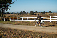 Backroads Trip Guest, Henry, Road Cycling Down Dirt Road at Chanslor Ranch, Bodega Bay, California