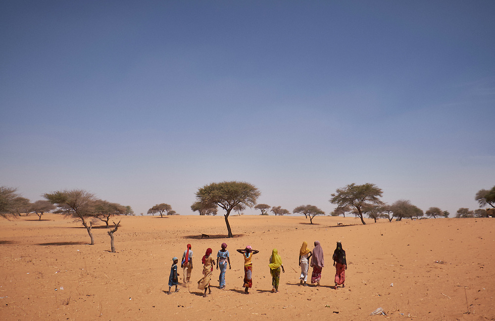 Girls walk through sand dunes in the village of Guidan Kaji near the border with Nigeria on the outskirts of Diffa, Niger on February 13, 2016. Displaced people from Niger and Nigeria are sheltering in the village after fleeing at the nearby border. Many of the families had witnessed attacks by Boko Haram in their villages or had fled because of other villages around them being attacked. Caritas undertook a distribution of sleeping covers, mosquito nets, pots and money transfers.