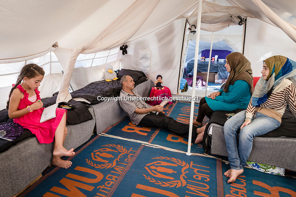 Greece, Lagkadikia, Dania ALKAMELL, age 9, from Idlip, Syria, is drawing, while here parents mother Tahany, her father Mohamad, age 50, and here sister Yara, age 13, are inside the tent relaxing taking time out from the camp.