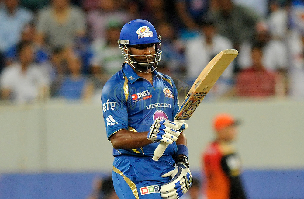 Kieron Pollard of the Mumbai Indians raises his bat after scoring  a half century during match 20 of the Pepsi Indian Premier League Season 2014 between the Mumbai Indians and the Sunrisers Hyderabad held at the Dubai International Stadium, Dubai, United Arab Emirates on the 30th April 2014<br /> <br /> Photo by Pal Pillia / IPL / SPORTZPICS