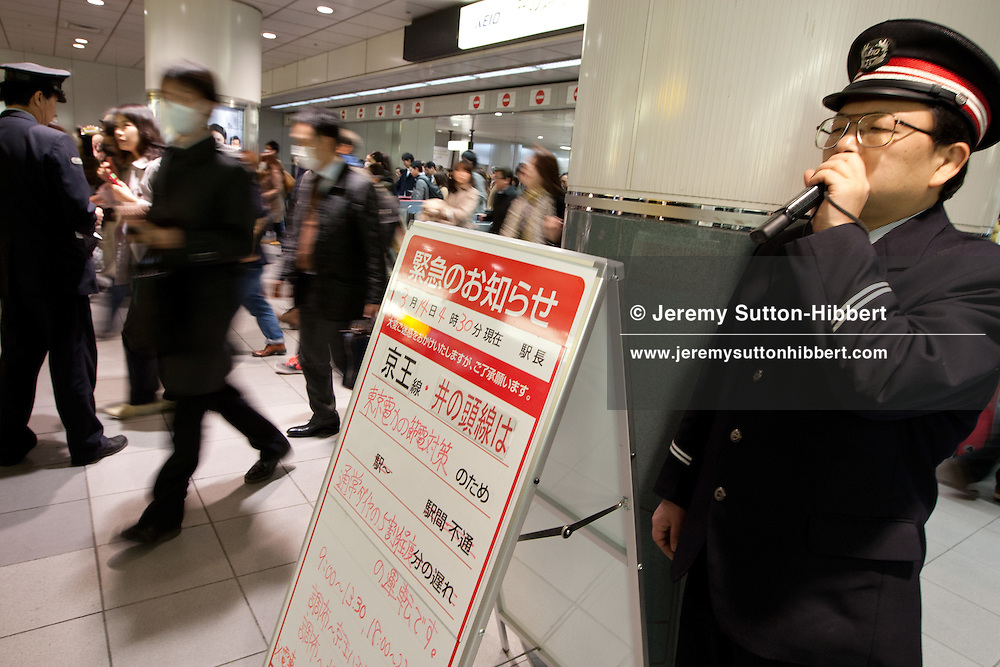 On the first business day since Friday's massive earthquake commuters faced train delays, shortages of trains and disruption on their Monday morning commute to work. Image shows commuters exiting the Inokashira train line and receiving compensation vouchers for future train travel due to the disruption from Keio train line staff, in Shibuya trains station in the Shibuya district of Tokyo, Japan, on Monday 14th March 2011.