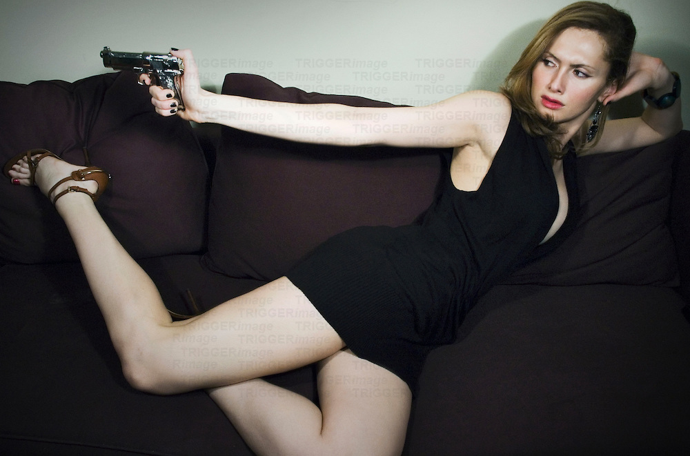 A young woman lying on a sofa holding a pistol