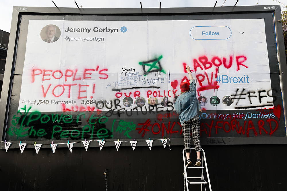 © Licensed to London News Pictures. 12/02/2019. London, UK.  Young anti-Brexit campaigners from the For our Future's Sake (FFS) wing of the People's Vote campaign in collaboration with the Led By Donkeys campaign write messages on a large billboard in Islington, stating why they want Jeremy Corbyn, the leader of the Labour Party to back a People's Vote on Brexit. The billboard, located in the Islington North constituency of Mr Corbyn shows messages reminding him that a majority of young Labour supporters want a public vote or second referendum on Brexit. Photo credit: Vickie Flores/LNP