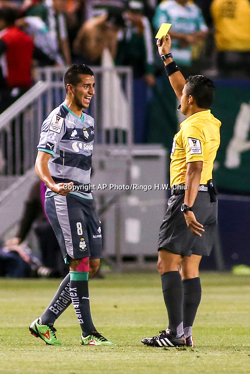 Referee, right, shows the yellow card to Santos Laguna midfielder Diego Gonzalez during the first half of a CONCACAF Champions League quarterfinal against Los Angeles Galaxy in Carson, Calif., Wednesday, Feb. 24, 2016. (AP Photo/Ringo H.W. Chiu)
