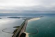 Nederland, Zeeland, Grevelingen, 19-10-2014;  de Brouwersdam, onderdeel van de Deltawerken (1971), tussen Goeree en Schouwen (aan de horizon), links het Grevelingenmeer en in het midden Middelplaat met recreatiecentrum en vakantiepark Port Zelande. Na het afsluiten van de zeearm Grevelingen zijn gaandeweg ernstige milieuproblemen in het nieuwe zoetwater ontstaan. De reeds in 1978 extra gebouwde doorlaatsluis, de Brouwerssluis (bij de uitstulping), heeft onvoldoende verlichting gebracht, er zijn nu plannen om een opening in de dam te maken om zo het getij deels terug te laten keren.<br /> Brouwersdam, part of the Delta Works (1971), between Goeree and Schouwen (on the horizon, province of Zeeland), Grevelingenmeer (l) with and holiday resort Middelplaat Port Zelande. After closing the estuary, gradually serious environmental problems have arisen in the newly created freshwater. A lock already built in 1978 brought not enough soalce, there are now plans for an opening in the dam so that the tide can partly return<br /> luchtfoto (toeslag op standard tarieven);<br /> aerial photo (additional fee required);<br /> copyright foto/photo Siebe Swart
