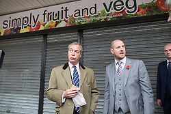 "© Licensed to London News Pictures . 03/11/2015 . Oldham , UK . UKIP leader NIGEL FARAGE (c) eating a pie in front of the soon to be opened UKIP Campaign HQ (formerly "" Simply Fruit and Veg "") in Royton Shopping Centre , at the launch of the party's campaign for the seat of Oldham West and Royton . The by-election has been triggered by the death of MP Michael Meacher . Photo credit : Joel Goodman/LNP"