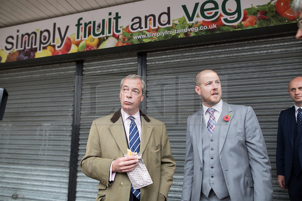 """© Licensed to London News Pictures . 03/11/2015 . Oldham , UK . UKIP leader NIGEL FARAGE (c) eating a pie in front of the soon to be opened UKIP Campaign HQ (formerly """" Simply Fruit and Veg """") in Royton Shopping Centre , at the launch of the party's campaign for the seat of Oldham West and Royton . The by-election has been triggered by the death of MP Michael Meacher . Photo credit : Joel Goodman/LNP"""