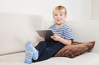 Portrait of happy young boy holding tablet PC on sofa