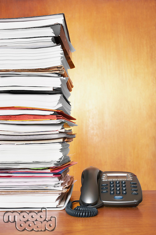 Stack of paperwork and telephone on desk